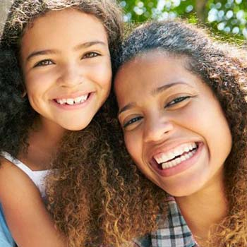 Mother and young daughter smiling outdoors
