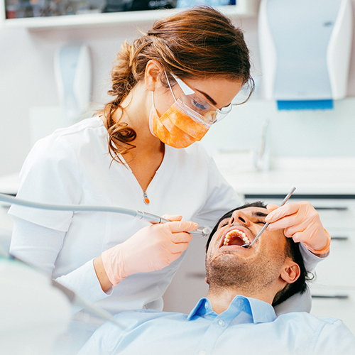 Male patient getting his teeth examined by a female hygienist