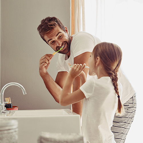 Dad and young daughter brushing their teeth